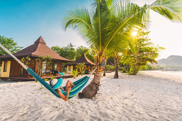Eine Frau in einer Hängematte am Strand vor dem Sivalai Beach Resort auf Koh Mook.