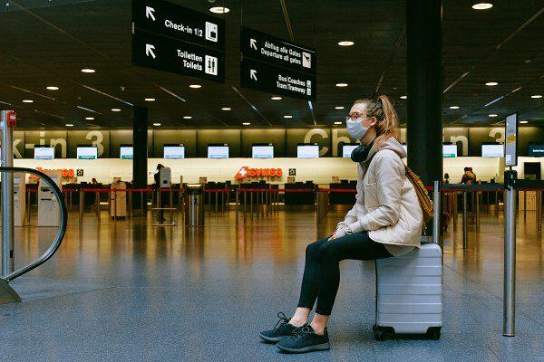 Eine Frau sitzt am Flughafen von Bangkok auf ihrem Koffer.
