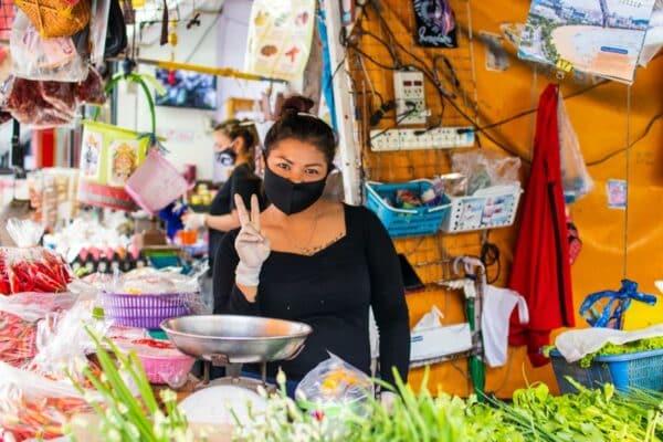 Marktfrau in Thailand mit Maske aufgrund der Maskenpflicht
