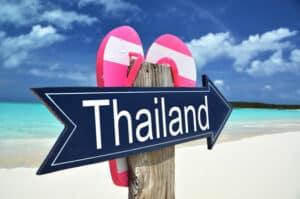 Schild mit dem Schriftzug Thailand an einem thailändischen Strand, mit Flip Flops.