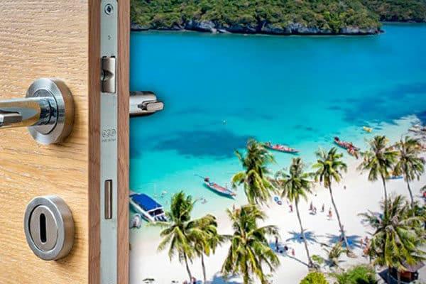 Eine Tür hinter der man ein Blick auf einen thailändischen Traumstrand hat.