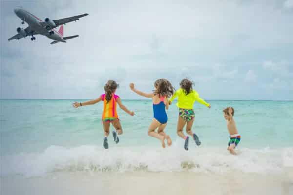 Kinder beim Spielen am Strand und ein Flugzeug befindet sich im Landeanflug auf Phuket