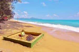 Ein Kind welches in einem Sandkasten am Strand von Phuket spielt.