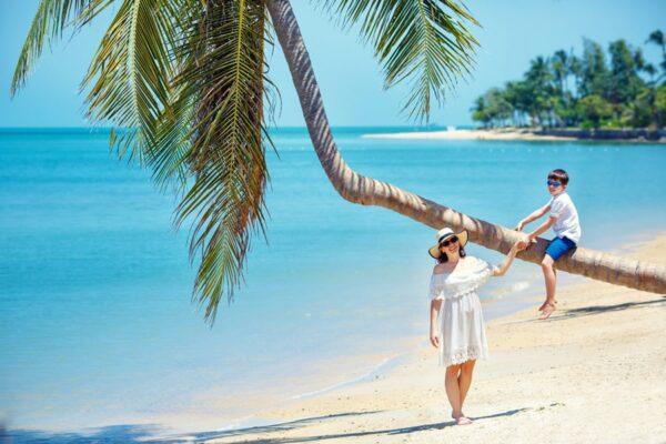 Mutter und kleiner Sohn am tropischen Strand sitzen auf einer Palme im Sommer Urlaub auf Koh Samui