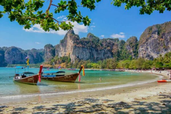 Strand von Raily, bei Krabi in Thailand mit einem typischen Longtailboot und badenden Touristen