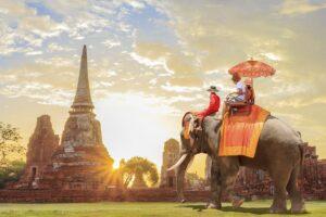 Touristen auf einem Elefantenritt durch die antike Stadt bei Sonnenaufgang