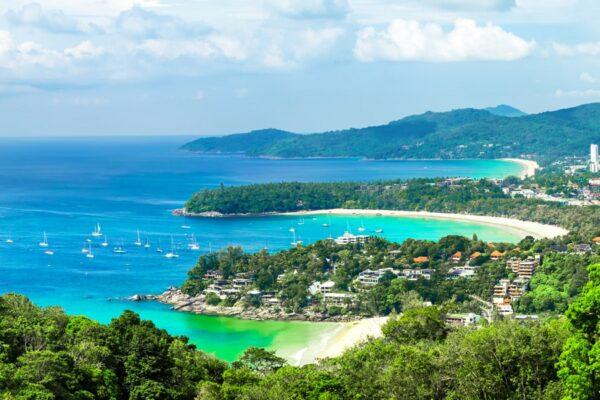 Wunderschöner türkisfarbener Ozean mit Wellen und Booten sowie eine Küste mit Stränden, aufgenommen vom Kata und Karon Strand Aussichtspunkt auf Phuket, Thailand
