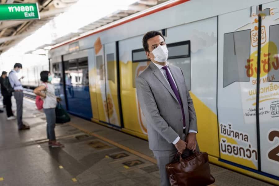 Ein thailaendischer Geschaeftsmann steht an einer BTS Skytrain Station in Bangkok, Thailand