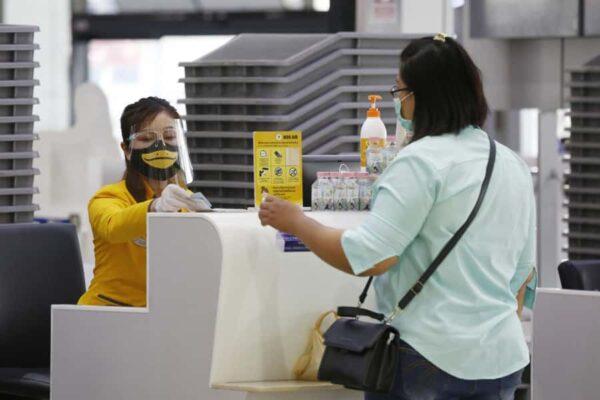 Passagierin am Schalter der Nok Air beim Einchecken für ihren Flug.