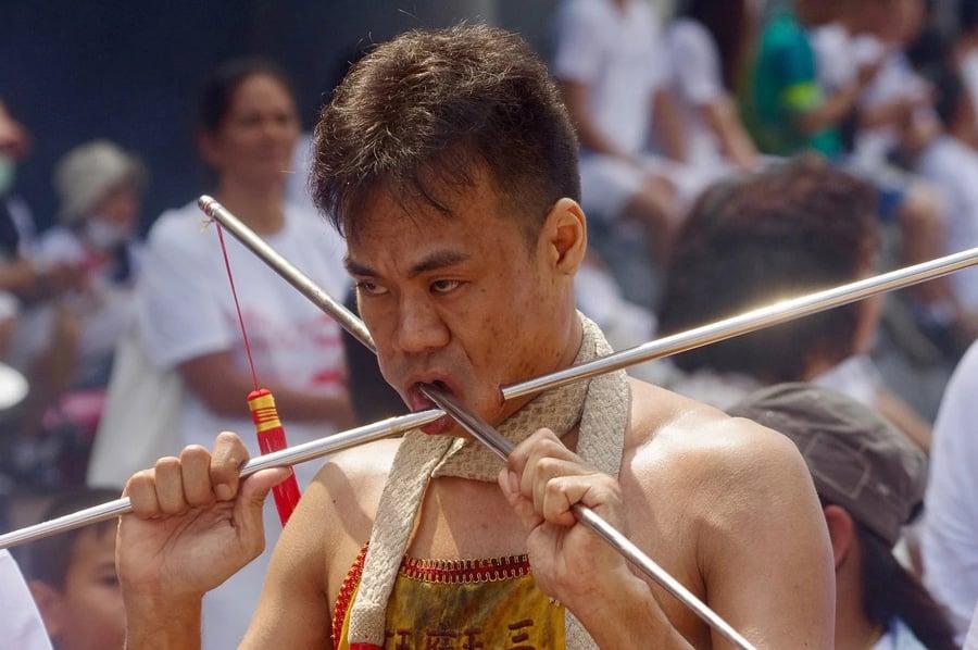 Ein Teilnehmer des Phuket Vegetarian Festival, der sich aus Tradition Schwerter durch die Backen sticht.