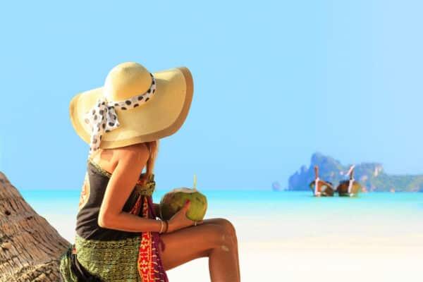 Eine Frau sitzt mit einer Kokosnuss am Strand und schaut auf das türkise Wasser, wo man auch ein paar Longtailboote findet.