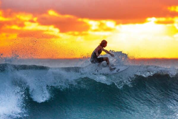 Ein Surfer beim Sonnenuntergang beim Wellenreiten vor Phuket